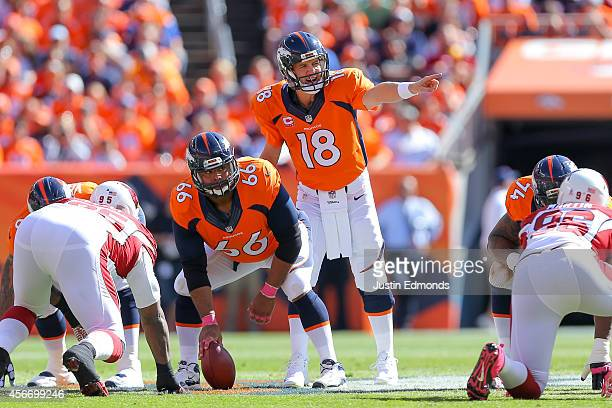 Quarterback Peyton Manning of the Denver Broncos runs the offense as center Manny Ramirez waits to snap the ball int he first quarter of a game...