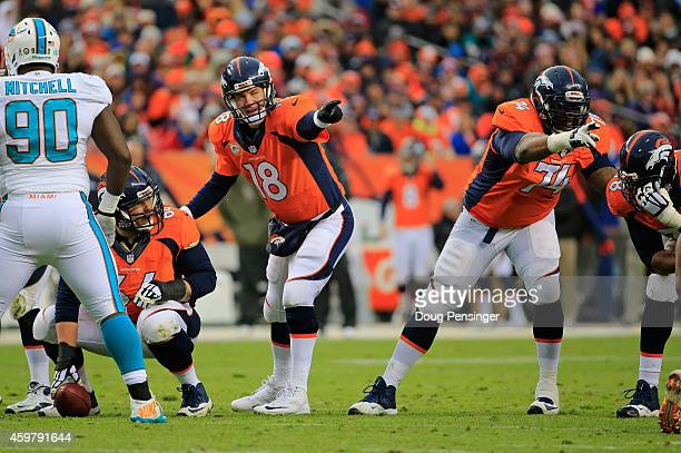 Quarterback Peyton Manning of the Denver Broncos runs the offense with center Will Montgomery and guard Orlando Franklin of the Denver Broncos...