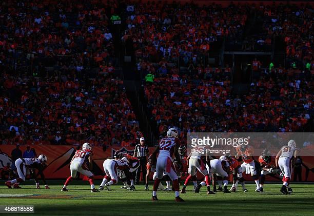 Quarterback Peyton Manning of the Denver Broncos takes the snap as the Denver Broncos offense takes on the Arizona Cardinals defense at Sports...