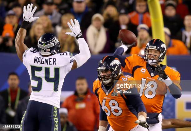 Quarterback Peyton Manning of the Denver Broncos throws an interception caught by strong safety Kam Chancellor and intended for tight end Julius...