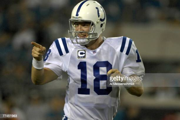 Quarterback Peyton Manning of the Indianapolis Colts points to the bench after tossing a touchdown pass against the Jacksonville Jaguars at the...