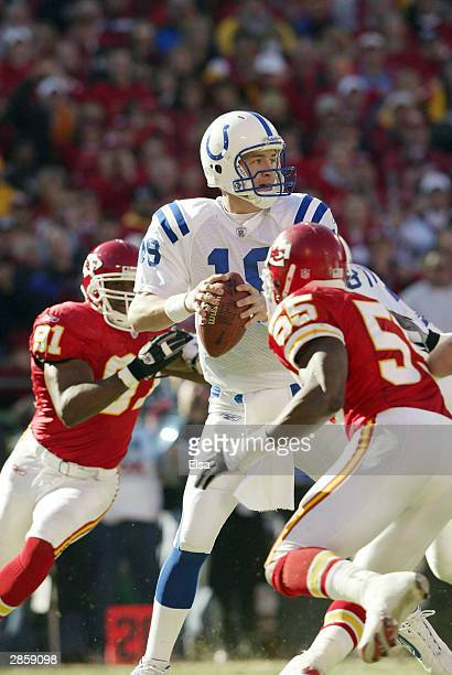 Quarterback Peyton Manning of the Indianapolis Colts prepares to throw a pass while under pressure from defensive tackle R-Kal Truluck and Gary...