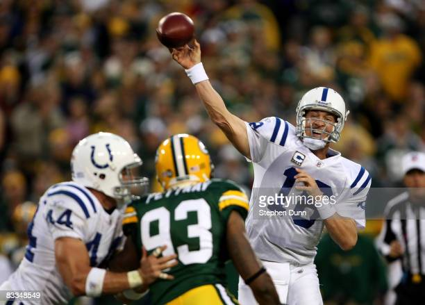 Quarterback Peyton Manning of the Indianapolis Colts throws a pass as tight end Dallas Clark blocks defensive end Kenny Pettway of the Green Bay...