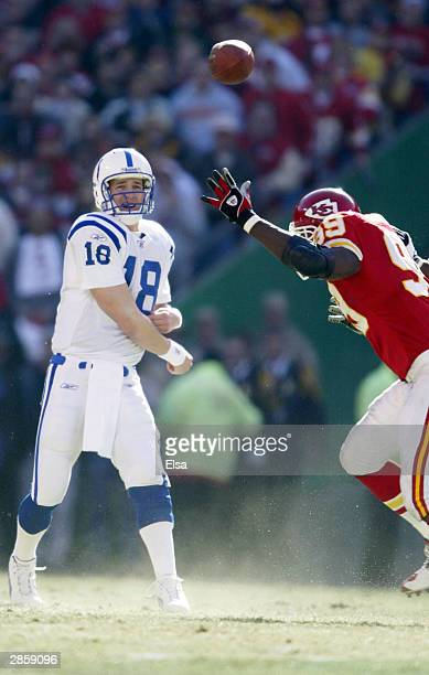Quarterback Peyton Manning of the Indianapolis Colts throws a pass while under pressure from defensive tackle Vonnie Holliday of the Kansas City...