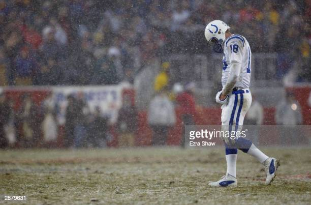 Quarterback Peyton Manning of the Indianapolis Colts walks onto the field as snow falls after the two minute warning in the first half against the...