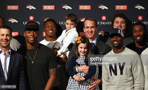Quarterback Peyton Manning poses with his daughter Mosley his son Marshall and former Denver Broncos teammates including Brandon Stokley Brandon...