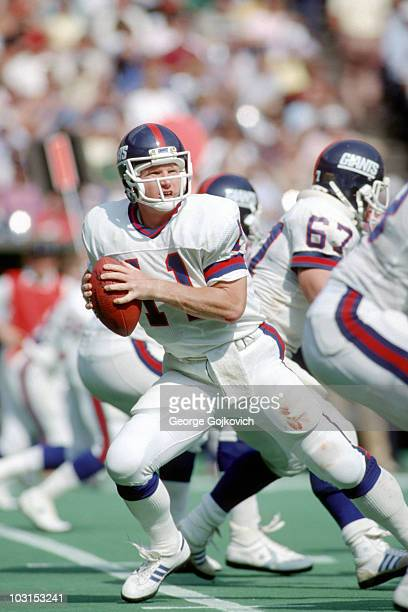 Quarterback Phil Simms of the New York Giants drops back to pass against the Cincinnati Bengals during a game at Riverfront Stadium on October 13...