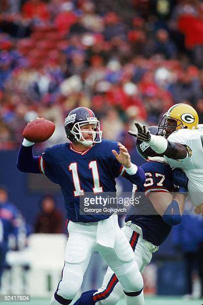 Quarterback Phil Simms of the New York Giants passes under pressure during an NFL game against the Green Bay Packers on December 19 1987 at Giants...