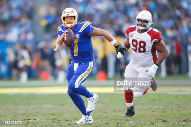 Quarterback Philip Rivers of the Los Angeles Chargers is forced out of the pocket by defensive tackle Corey Peters of the Arizona Cardinals in the...