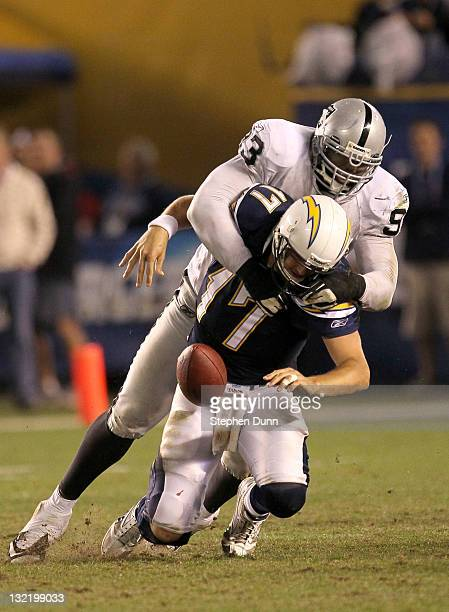 Quarterback Philip Rivers of the San Diego Chargers loses the football as he is sacked on the final play of the game by defensive lineman Tommy Kelly...