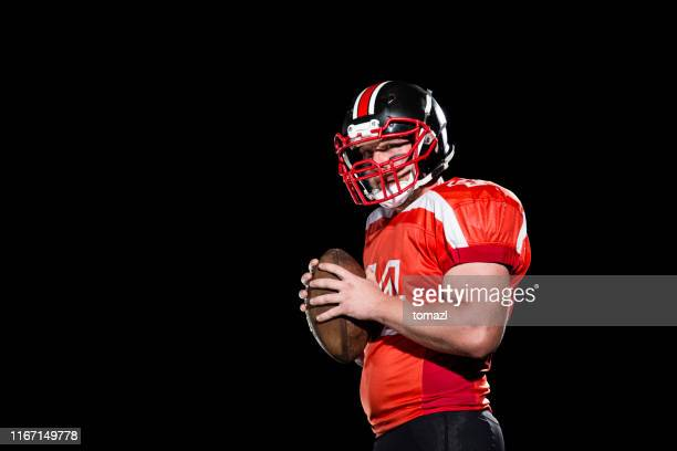 quarterback portrait on black background - football player stock pictures, royalty-free photos & images