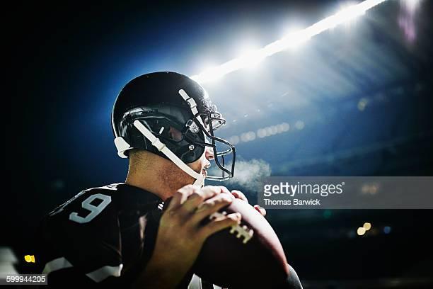 Quarterback preparing to throw pass at night