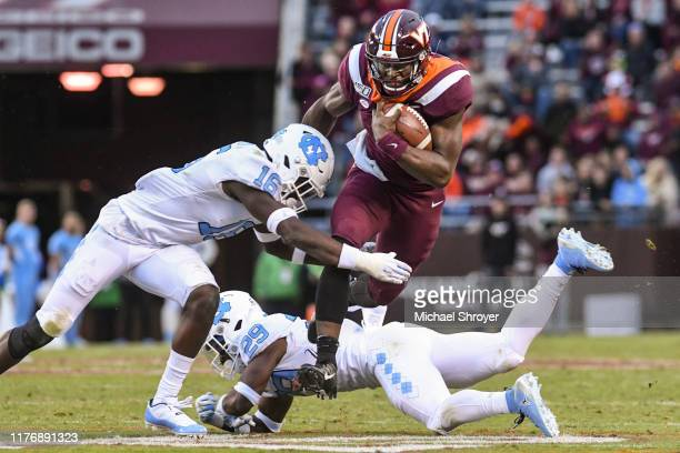 Quarterback Quincy Patterson II of the Virginia Tech Hokies carries the ball as defensive back DJ Ford and defensive back Storm Duck of the North...