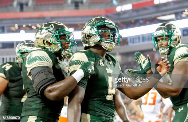 Quarterback Quinton Flowers of the South Florida Bulls is congratulated by teammates after scoring a touchdown against Illinois Fighting Illini at...