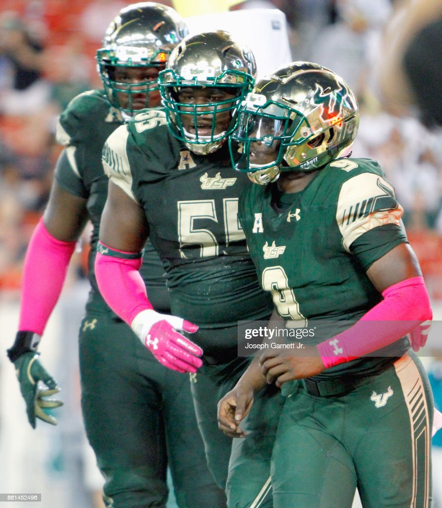 Quarterback Quinton Flowers #9 of the South Florida Bulls runs off the field with teammate offensive lineman Eric Mayes #55 after scoring a touchdown against the Cincinnati Bearcats during the third quarter of their game at Raymond James Stadium on October 14, 2017 in Tampa, Florida.