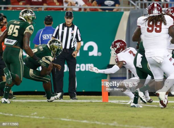 Quarterback Quinton Flowers of the South Florida Bulls rushes 22 yards for a touchdown while getting pressure from defensive back Sean Chandler of...