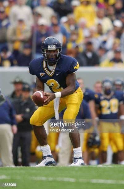Quarterback Rasheed Marshall of the West Virginia University Mountaineers looks for an open man against the University of Miami Hurricanes during a...
