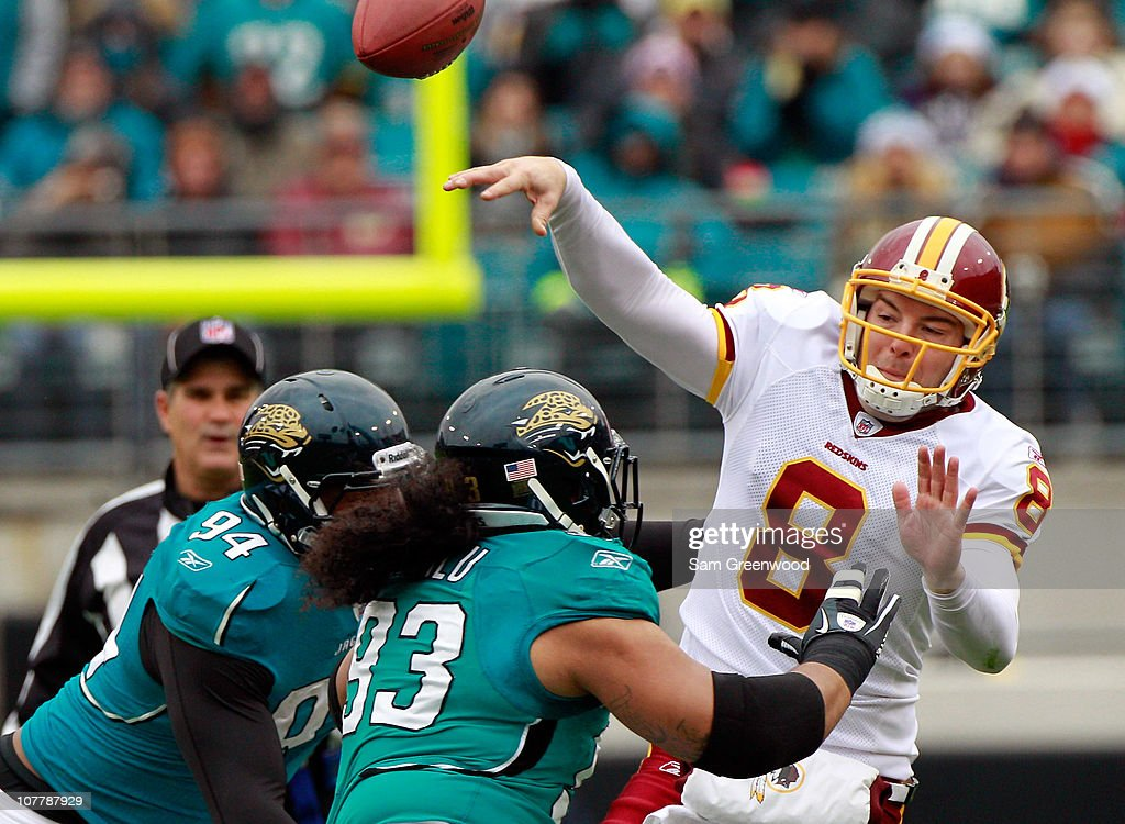 Quarterback Rex Grossman #8 of the Washington Redskins is pressured by Tyson Alualu #93 and Jeremy Mincey #94 of the Jacksonville Jaguars during the game at EverBank Field on December 26, 2010 in Jacksonville, Florida.