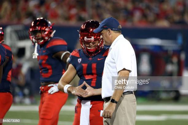 Quarterback Rhett Rodriguez of the Arizona Wildcats shakes hands with his father head coach Rich Rodriguez before the start of the college football...