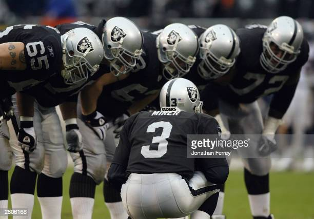 Quarterback Rick Mirer of the Oakland Raiders huddles with the team during the game against the Denver Broncos on November 30 2003 at Network...