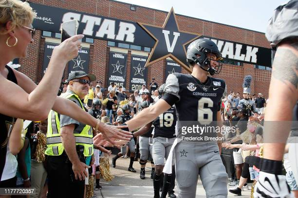 Quarterback Riley Neal of the Vanderbilt Commodores high fives a fan as he walks to the stadium prior to a game against the Northern Illinois Huskies...