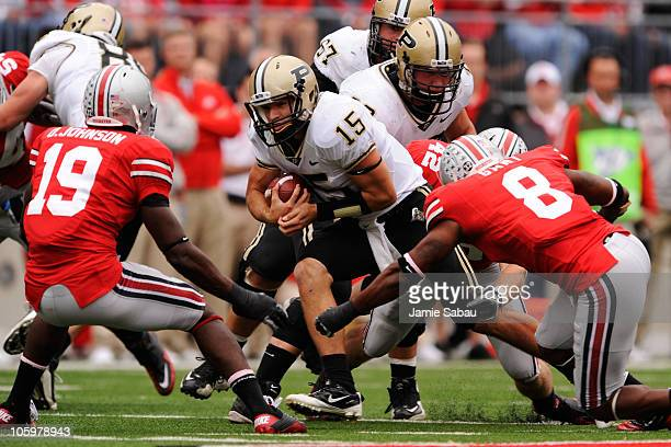 Quarterback Rob Henry of the Purdue Boilermakers looks for running room as Orhian Johnson of the Ohio State Buckeyes and Aaron Gant of the Ohio State...