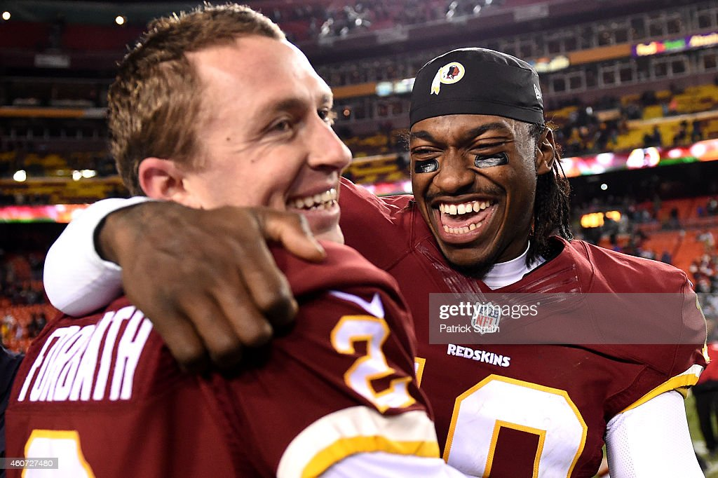 Quarterback Robert Griffin III #10 celebrates with kicker Kai Forbath #2 of the Washington Redskins after defeating the Philadelphia Eagles at FedExField on December 20, 2014 in Landover, Maryland. The Washington Redskins won, 27-24.