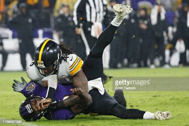 Quarterback Robert Griffin III of the Baltimore Ravens takes a hit from outside linebacker Bud Dupree of the Pittsburgh Steelers during the second...