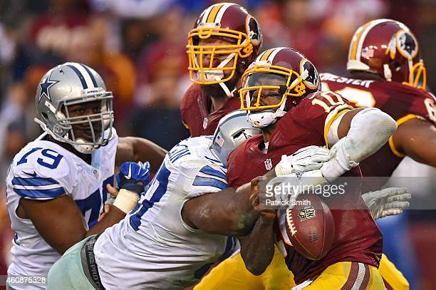 Quarterback Robert Griffin III of the Washington Redskins fumbles the ball as he is sacked by defensive tackle Terrell McClain of the Dallas Cowboys...