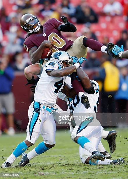 Quarterback Robert Griffin III of the Washington Redskins is tackled by Captain Munnerlyn and James Anderson of the Carolina Panthers during the...