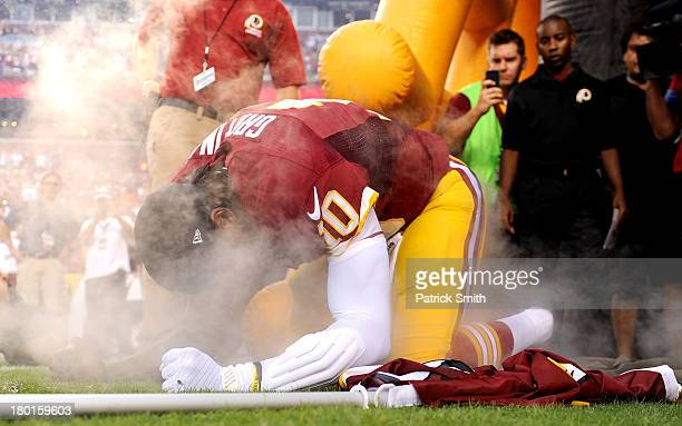Quarterback Robert Griffin III of the Washington Redskins kneels down before he leads the team out onto the field before taking on the Philadelphia...