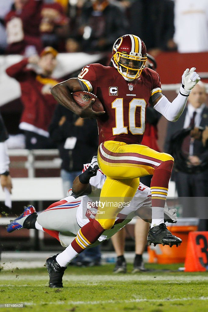 Quarterback Robert Griffin III #10 of the Washington Redskins runs for a 46-yard gain as he is taken down by Stevie Brown #27 of the New York Giants in the second half at FedExField on December 3, 2012 in Landover, Maryland.