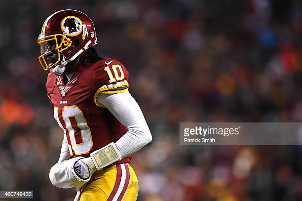 Quarterback Robert Griffin III of the Washington Redskins runs off the field against the Philadelphia Eagles at FedExField on December 20 2014 in...