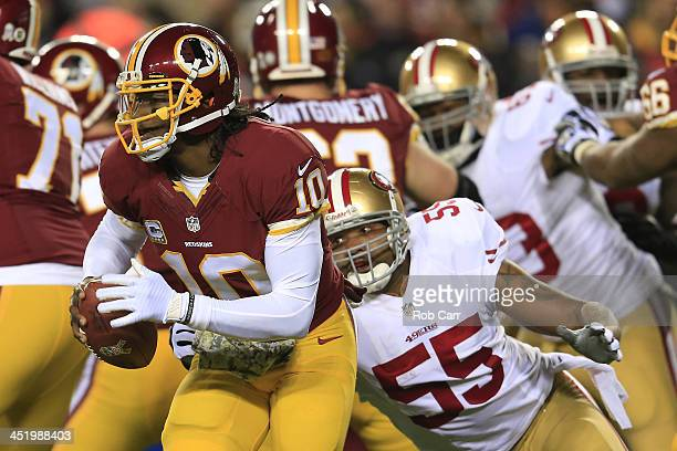 Quarterback Robert Griffin III of the Washington Redskins runs the ball as outside linebacker Ahmad Brooks of the San Francisco 49ers rushes in in...