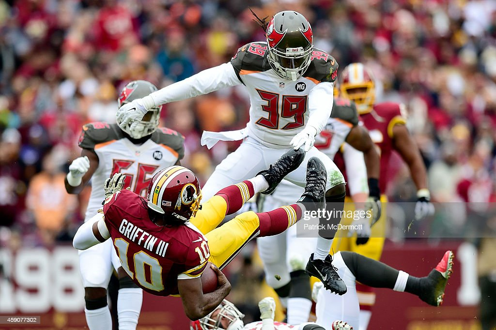 Quarterback Robert Griffin III #10 of the Washington Redskins takes a second quarter hit from defensive back Brandon Dixon #39 of the Tampa Bay Buccaneers at FedExField on November 16, 2014 in Landover, Maryland.