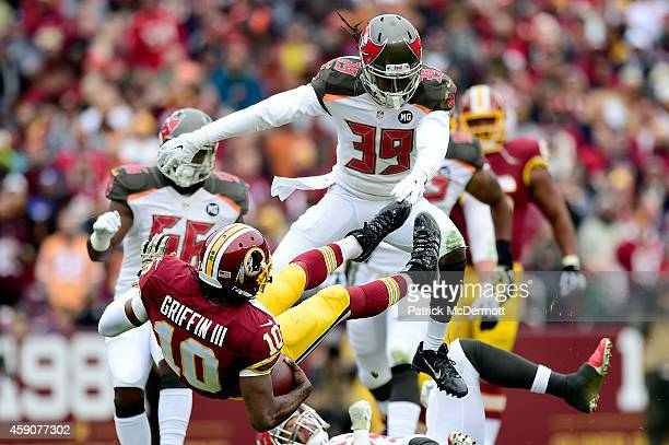 Quarterback Robert Griffin III of the Washington Redskins takes a second quarter hit from defensive back Brandon Dixon of the Tampa Bay Buccaneers at...