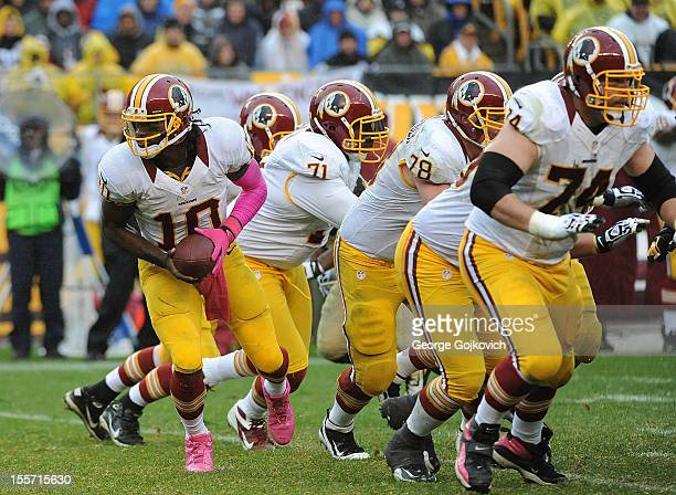 Quarterback Robert Griffin III of the Washington Redskins turns to handoff the football behind the blocking of offensive linemen Trent Williams Kory...