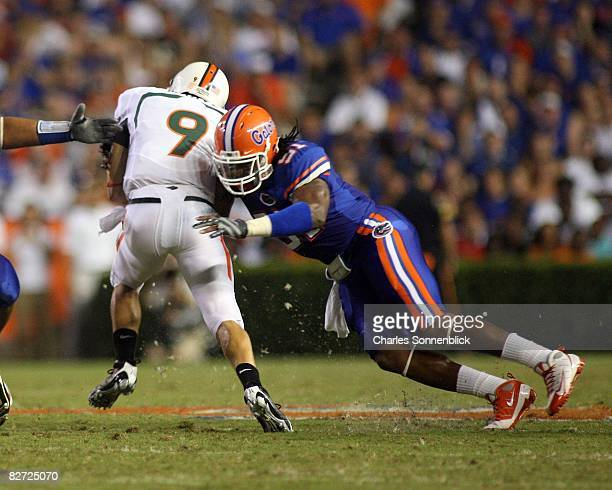 Quarterback Robert Marve of the Miami Hurricanes runs for a few yards before being tackled by linebacker Brandon Spikes of the Florida Gators on...