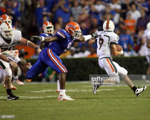 Quarterback Robert Marve of the Miami Hurricanes runs for a few yards before being tackled by defensive end Carlos Dunlap of the Florida Gators on...