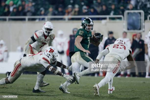 Quarterback Rocky Lombardi of the Michigan State Spartans avoids defensive back Saquan Hampton of the Rutgers Scarlet Knights and defensive back Kiy...