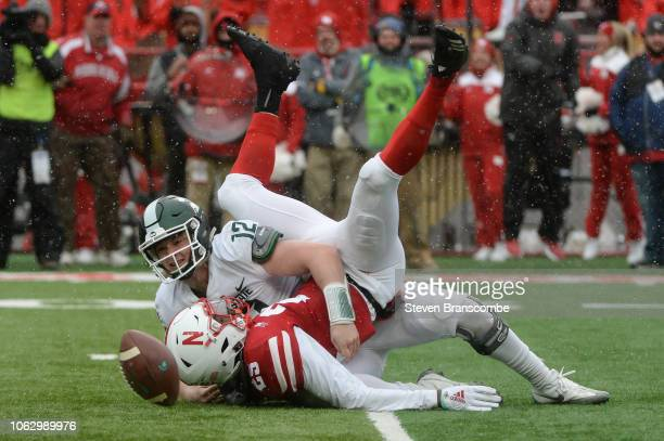 Quarterback Rocky Lombardi of the Michigan State Spartans fumbles after a sack by defensive back Antonio Reed of the Nebraska Cornhuskers in the...