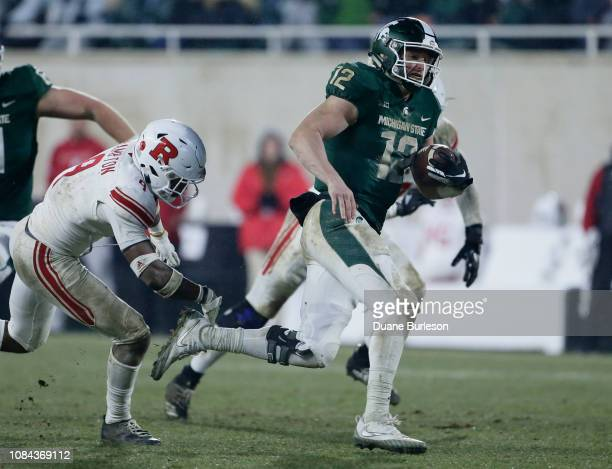 Quarterback Rocky Lombardi of the Michigan State Spartans is pursued by defensive back Saquan Hampton of the Rutgers Scarlet Knights during the...