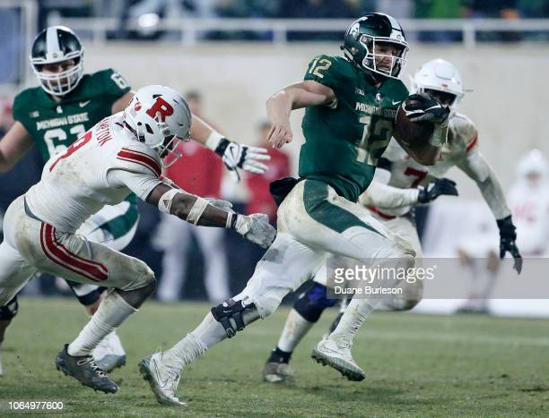 Quarterback Rocky Lombardi of the Michigan State Spartans scrambles against defensive back Saquan Hampton of the Rutgers Scarlet Knights and...