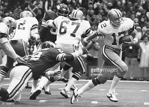 Quarterback Roger Staubach of the Dallas Cowboys scrambles as he avoids the tackle by Doug Sutherland of the Minnesota Vikings during a 1978 NFL game...