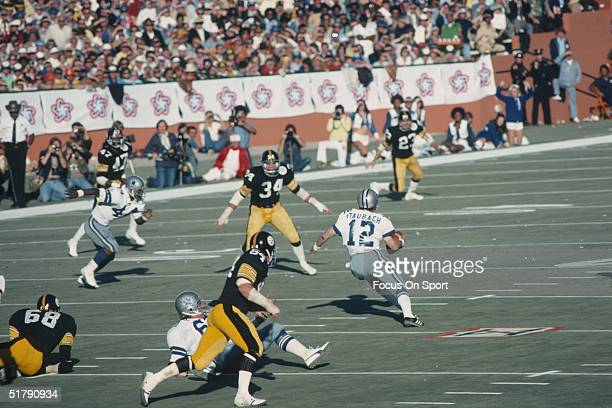 Quarterback Roger Staubach of the Dallas Cowboys scrambles for yards against the Pittsburgh Steelers defense during Super Bowl X at the Orange Bowl...