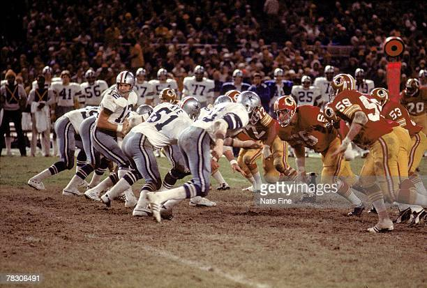 Quarterback Roger Staubach of the Dallas Cowboys turn to handoff against the Washington Redskins at RFK Stadium on October 31 1976 in Washington DC...