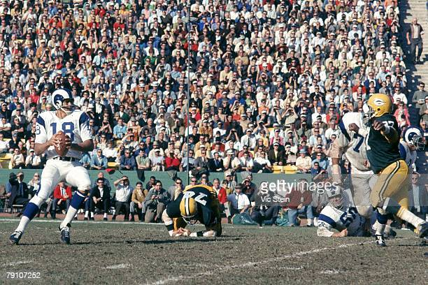 Quarterback Roman Gabriel of the Los Angeles Rams drops back to pass as defensive end Willie Davis of the Green Bay Packers applies pressure at the...