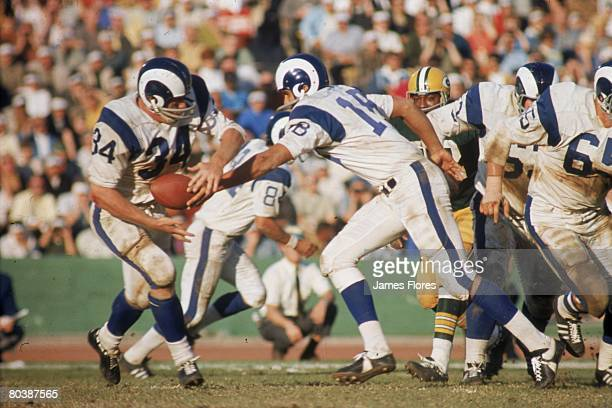 Quarterback Roman Gabriel of the Los Angeles Rams turns to handoff to running back Les Josephson in an NFL game against the Green Bay Packers at the...
