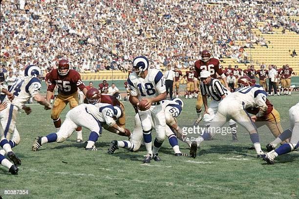 Quarterback Roman Gabriel of the the Los Angeles Rams turns to handoff during an NFL game against the Washington Redskins at the Los Angeles Memorial...