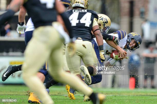 Quarterback Ross Bowers of the California Golden Bears is sacked by linebacker Drew Lewis of the Colorado Buffaloes in the second quarter of a game...